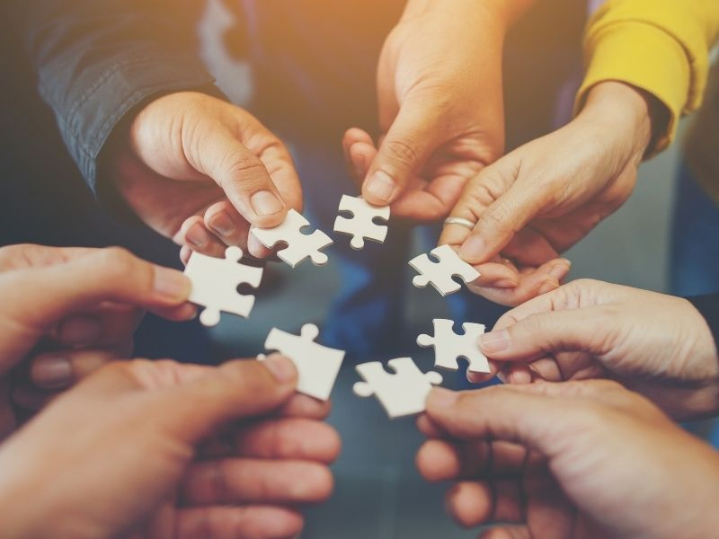 people's hands with puzzle pieces