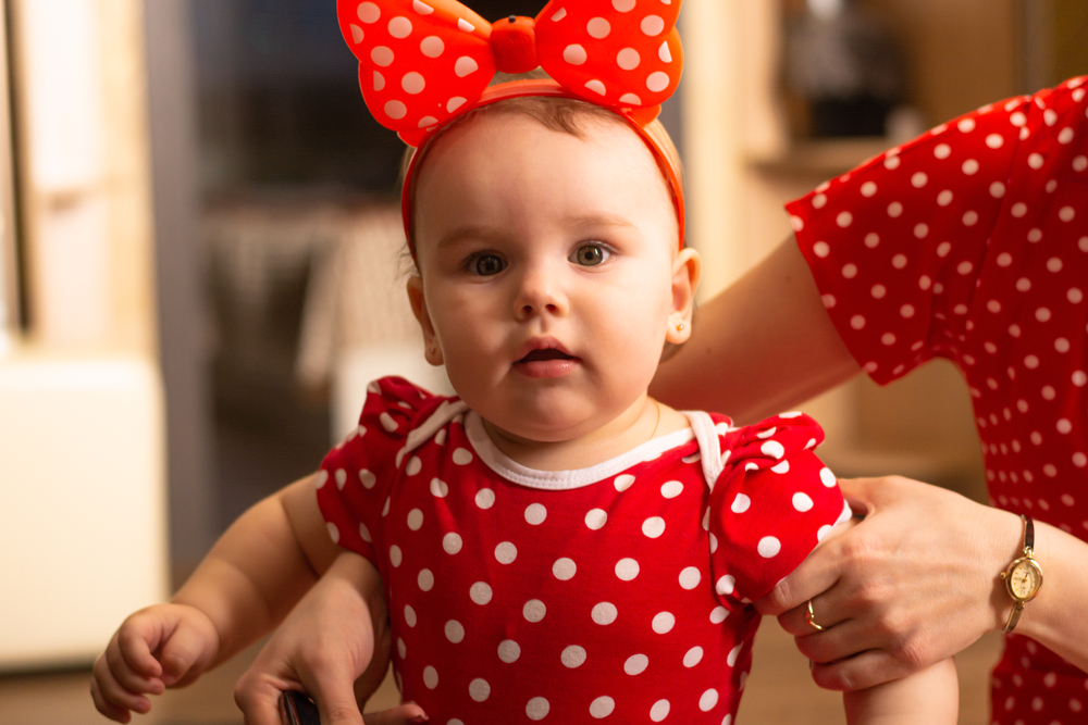 Cute one year old girl dressed up in a polka dot red dress