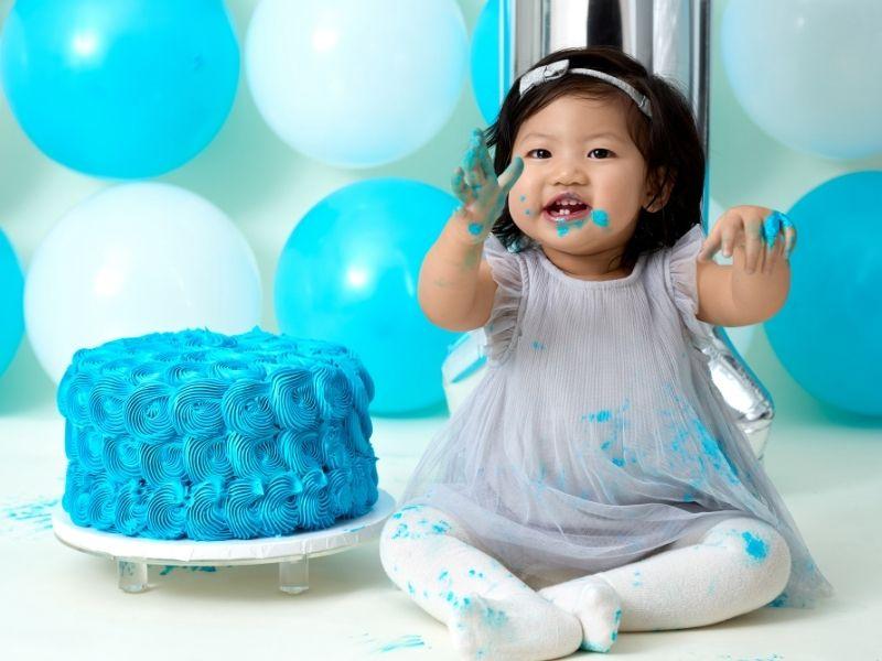 toddler working on a blue cake smash