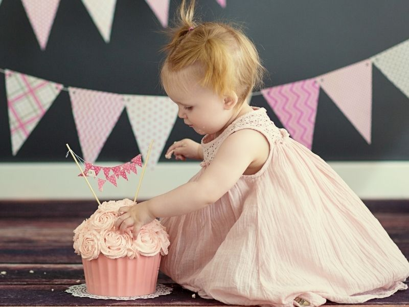 cute one year old girl checking out her smash cake