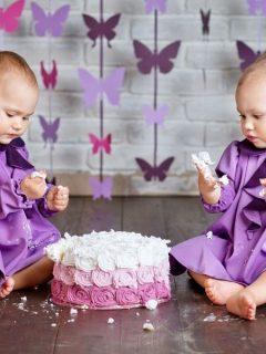 adorable twin girls enjoying their first birthday cake