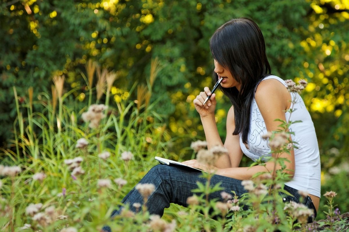 a young woman writing in her journal sitting on the grass