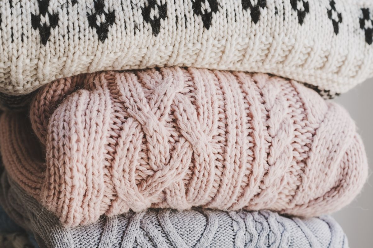 a stack of handmade sweaters